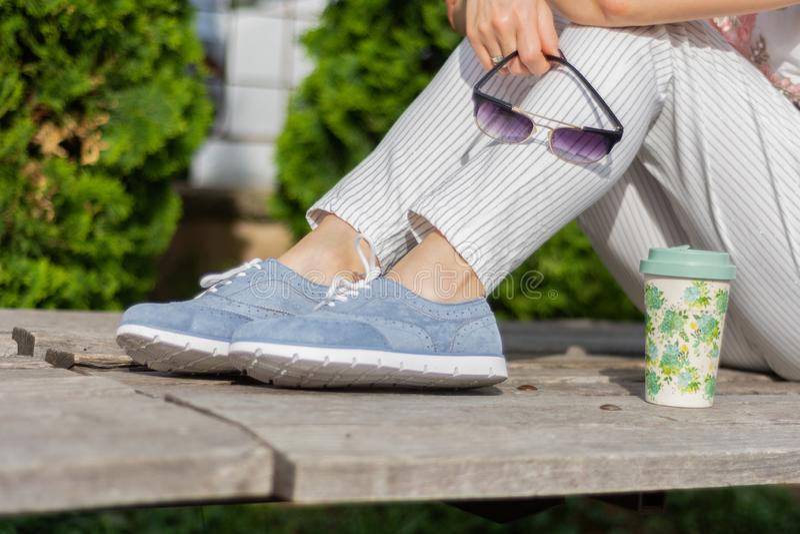 有镶边坐一条长凳在公园和拿着太阳镜,在女孩旁边的咖啡杯的裤子和蓝色运动鞋的一名现代妇女 图库摄影