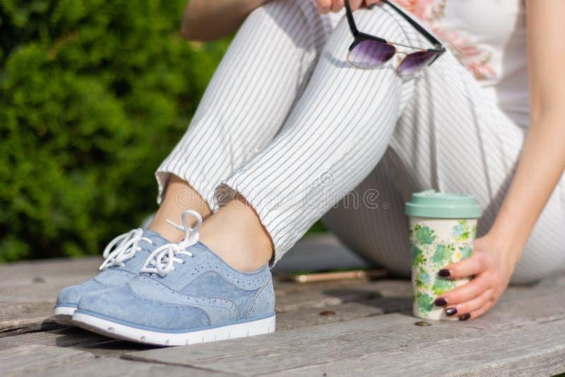 有镶边裤子的时兴的女孩腿和蓝色运动鞋和一点光秃的皮肤在拿着太阳镜和咖啡的腿 库存图片