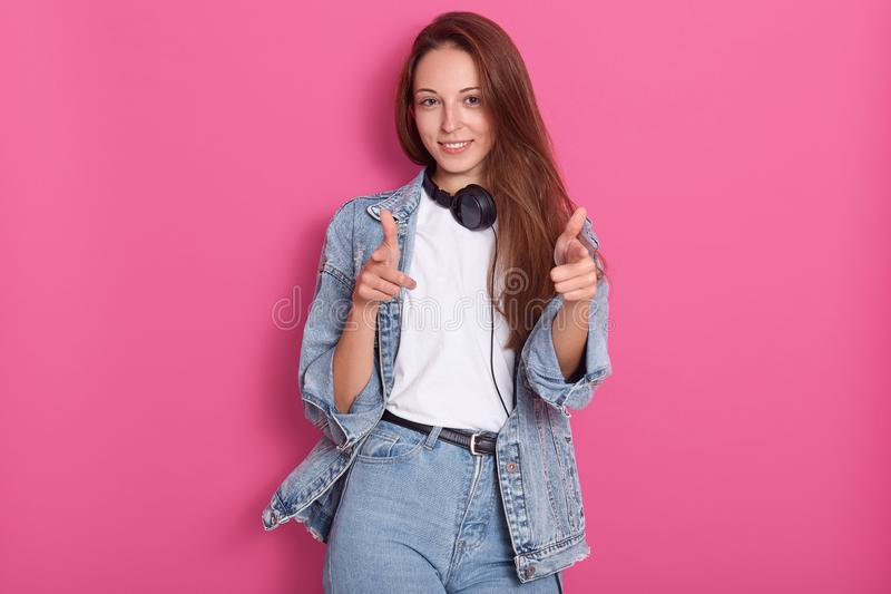 有长发、佩带的白色偶然T恤杉、牛仔裤和牛仔布夹克的正面快乐的年轻白种人妇女,拿着耳机 免版税图库摄影