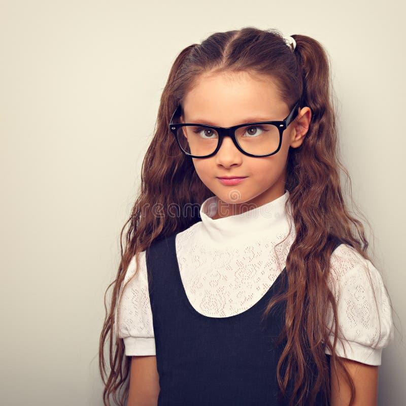 有长发发型的做鬼脸的学生女孩在一致的半眯着眼睛看的眼睛的时尚镜片 库存照片
