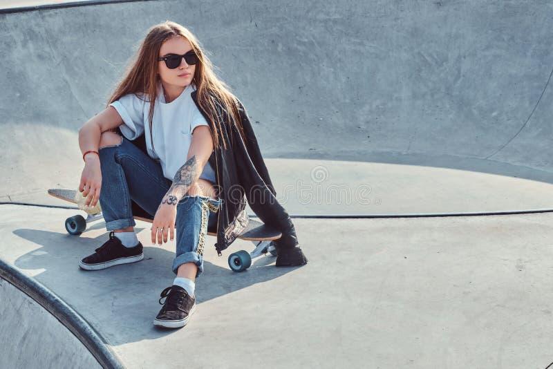 有长发和太阳镜的时髦年轻女人坐在skatepark 免版税库存照片