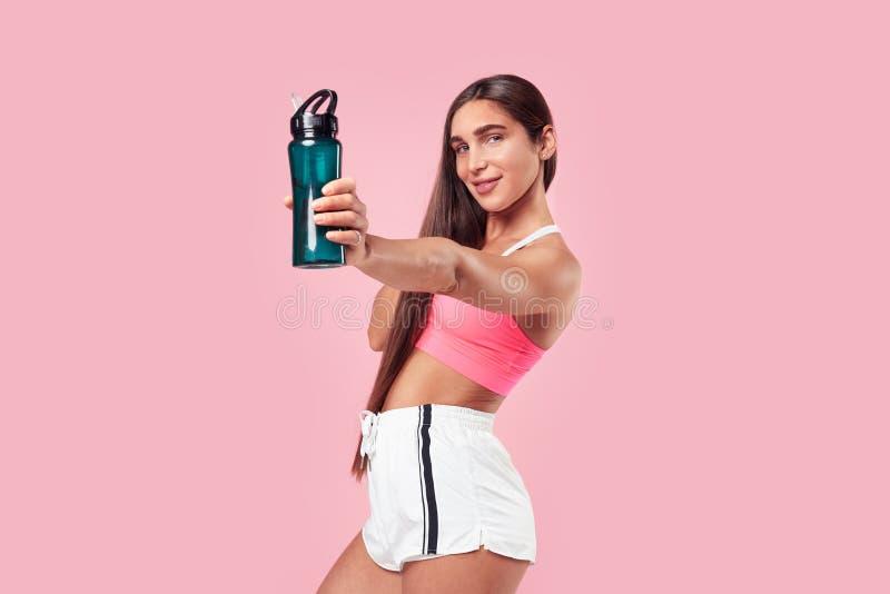 有长发强健的身体的妇女在放松在锻炼以后的体育衣物,显示水botle在桃红色背景的 免版税库存照片