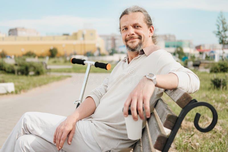 有长发的一个可爱的年长50岁的人在尾巴在一个公园里坐长凳 E 免版税库存照片
