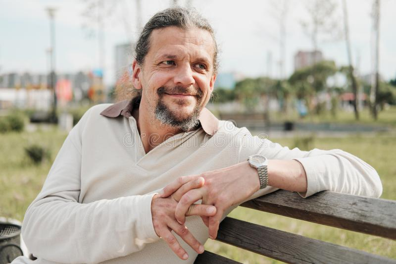 有长发的一个可爱的年长50岁的人在尾巴在一个公园里坐长凳 E 免版税图库摄影