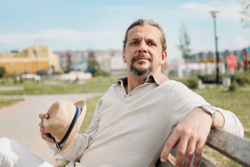 有长发的一个可爱的年长50岁的人在尾巴在一个公园里坐长凳 E 图库摄影