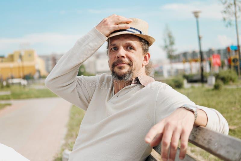 有长发的一个可爱的年长50岁的人在尾巴在一个公园里坐长凳 E 库存照片