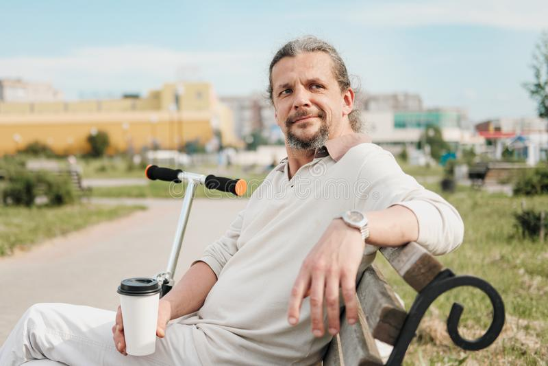 有长发的一个可爱的年长50岁的人在尾巴在一个公园里坐长凳 E 免版税库存图片