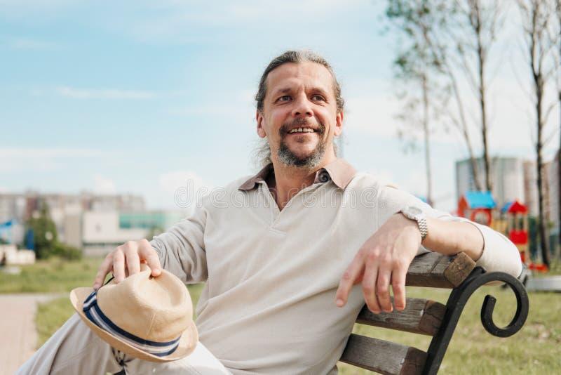 有长发的一个可爱的年长50岁的人在尾巴在一个公园里坐长凳 E 库存图片
