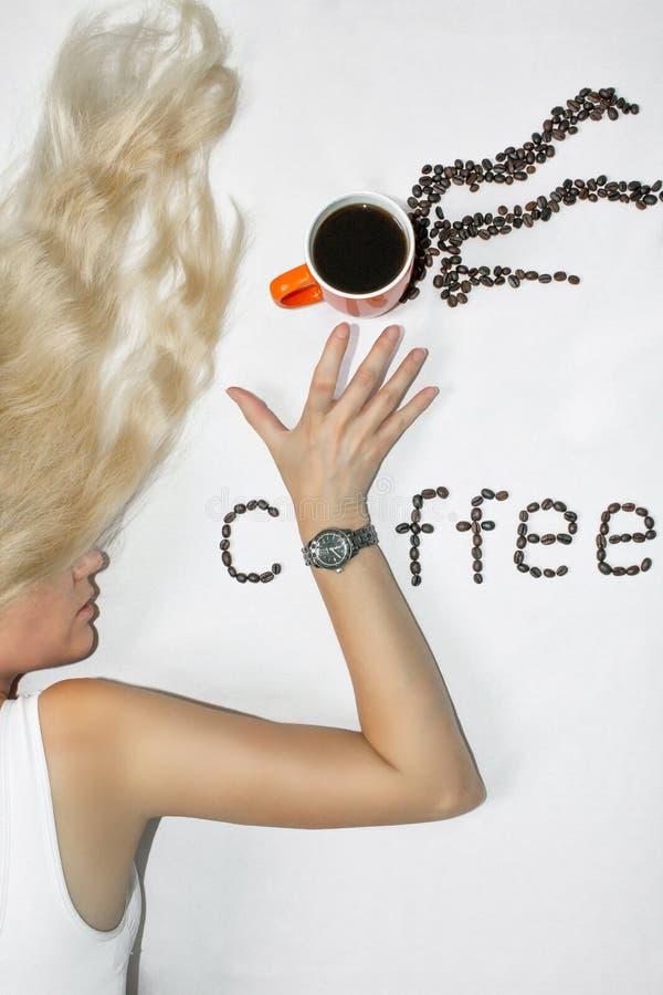有长发的一名年轻白肤金发的妇女伸她的有时钟的手延长在一杯咖啡,在白色背景 的treadled 库存照片