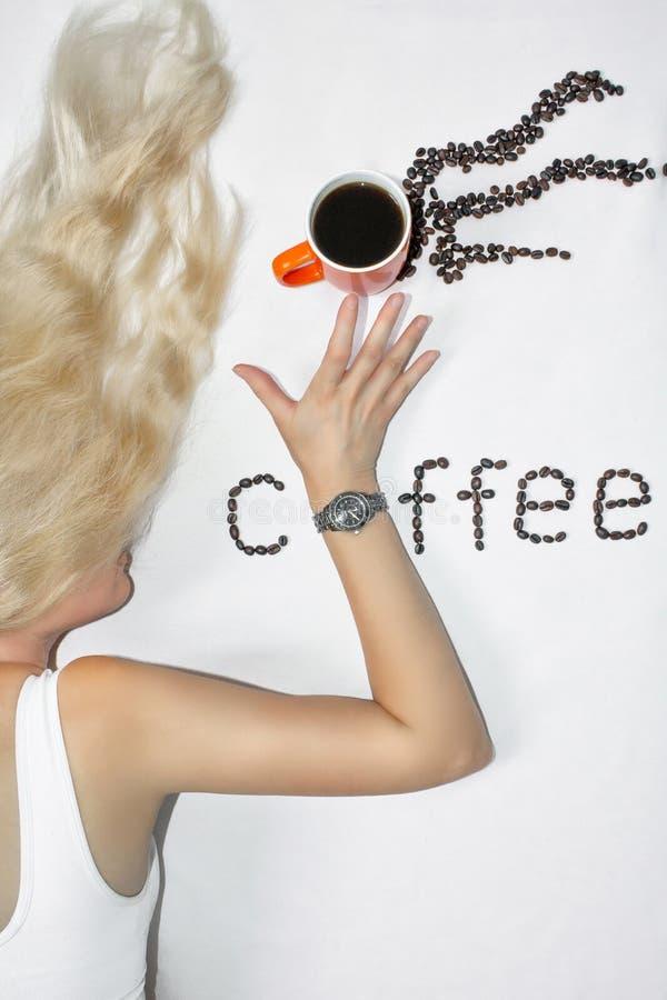 有长发的一名年轻白肤金发的妇女伸她的有时钟的手延长在一杯咖啡,在白色背景 的treadled 免版税库存图片