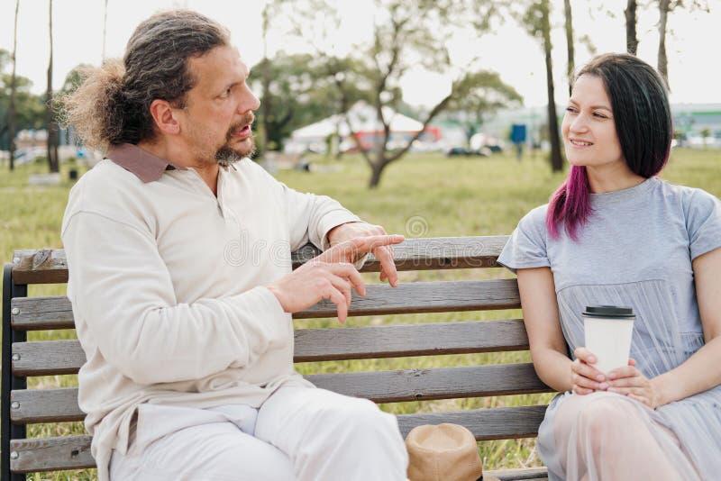 有长发的一年长帅哥在尾巴和一年轻美女坐公园长椅和聊天 免版税库存照片