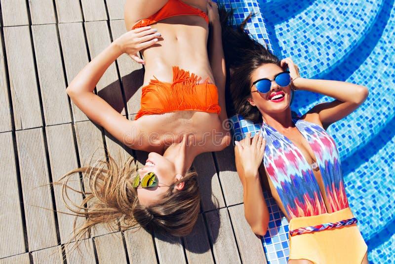 有长发的两个可爱的白肤金发和深色的女孩在弗洛尔说谎在水池附近 他们穿比基尼泳装和泳装 ?? 库存图片