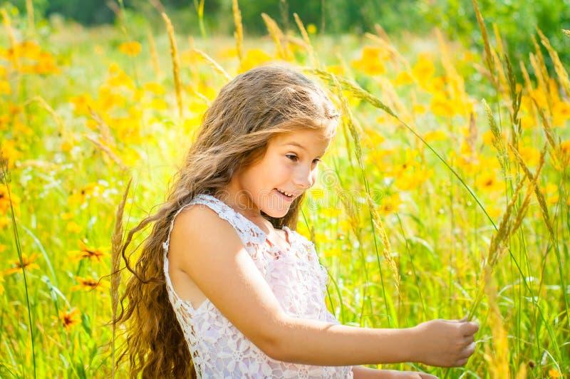 有长发的女孩在一件白色礼服在与花的一个领域高兴 免版税库存图片