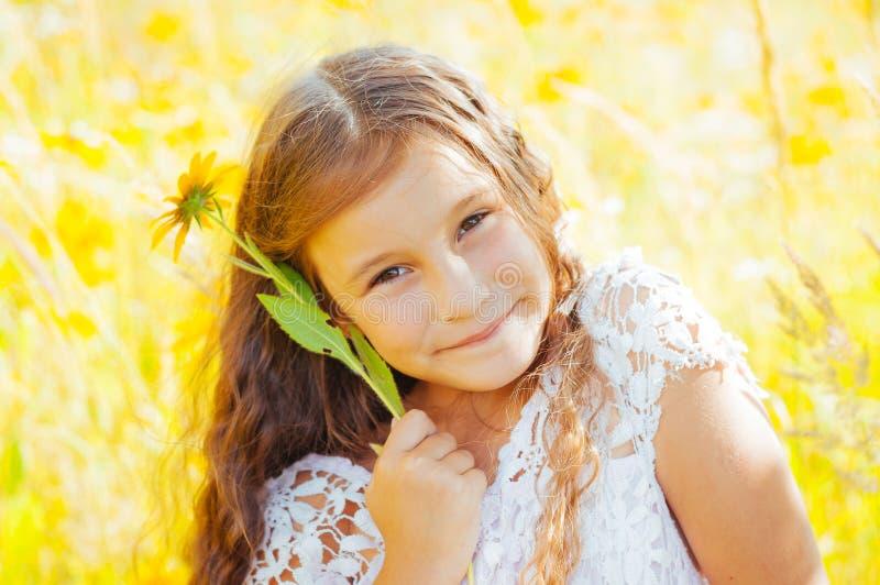 有长发的女孩在一件白色礼服在与花的一个领域高兴 免版税库存照片