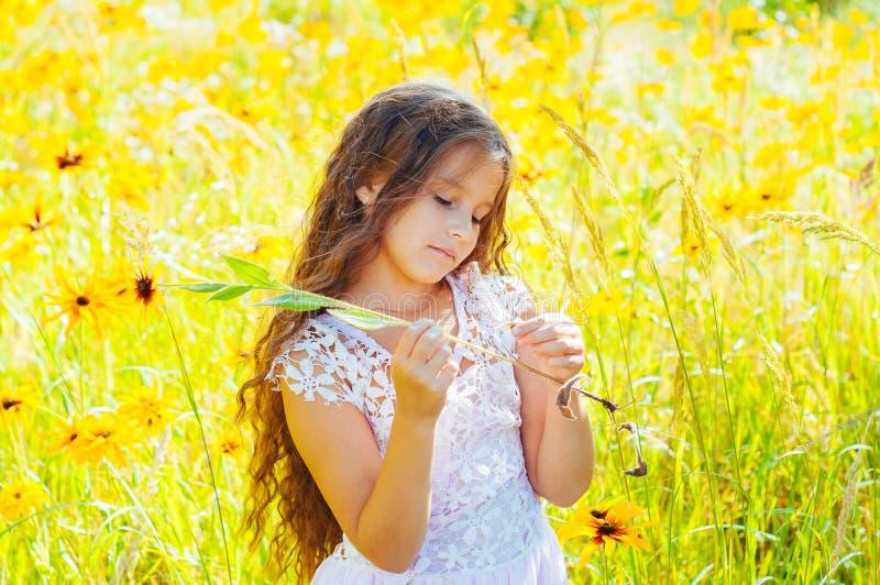 有长发的女孩在一件白色礼服在与花的一个领域高兴 库存照片
