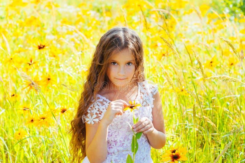 有长发的女孩在一件白色礼服在与花的一个领域高兴 图库摄影