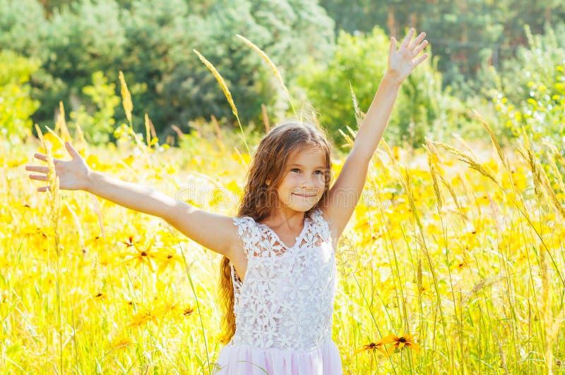 有长发的女孩在一件白色礼服在与花的一个领域高兴 库存图片