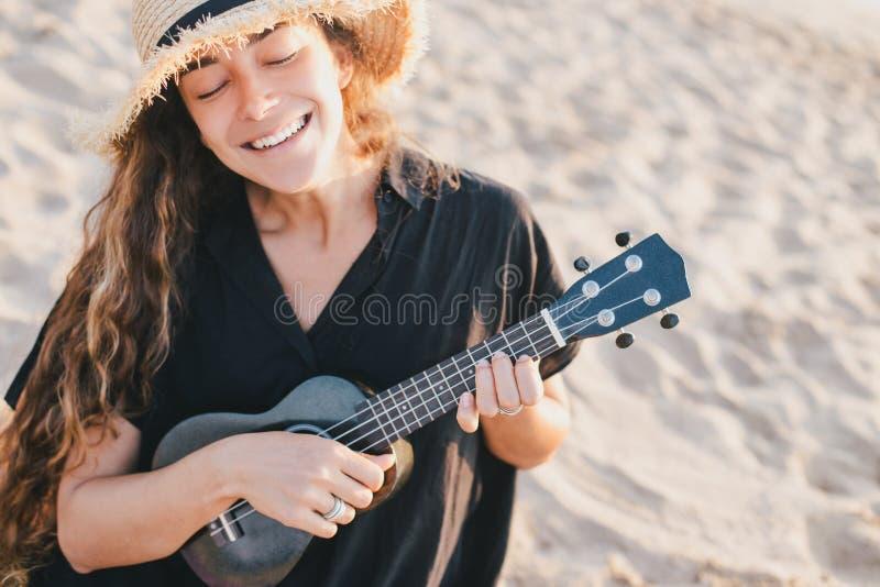 有长发的妇女在演奏尤克里里琴的帽子在海滩 免版税库存图片