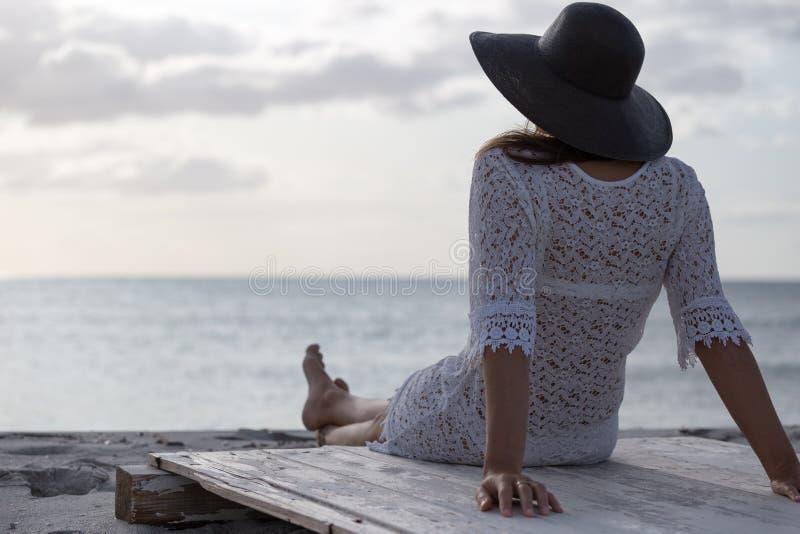 有长发的年轻女人从坐由海看看的后面天际在风的黎明,穿戴在一件白色鞋带礼服 库存图片