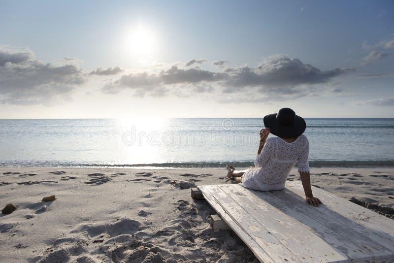 有长发的年轻女人从坐由海看看的后面天际在风的黎明,穿戴在一件白色鞋带礼服 库存照片