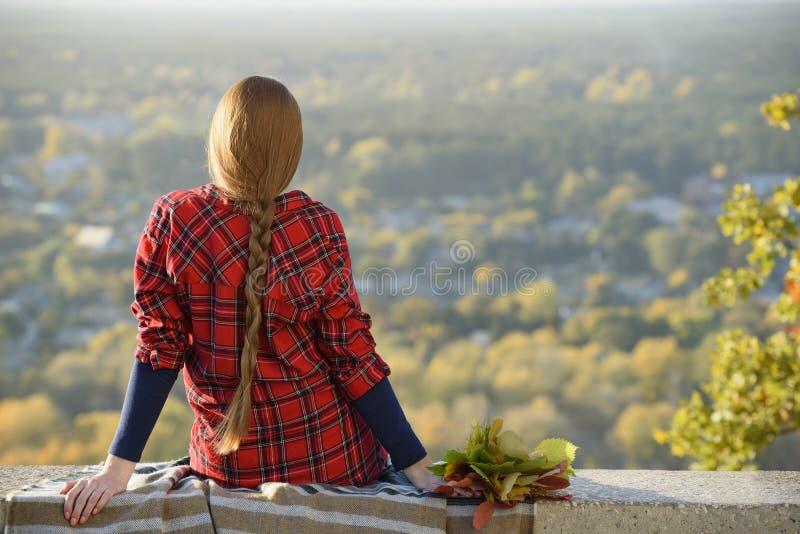 有长发的年轻女人坐俯视城市的小山 免版税库存照片