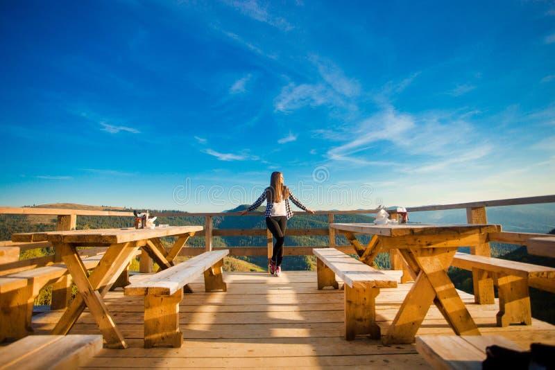有长发的年轻女人有休息在露天咖啡馆在山顶部并且享受看法 免版税库存照片