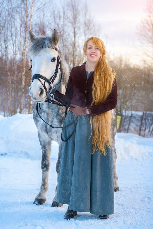 有长发的年轻女人有马的在冬天 图库摄影