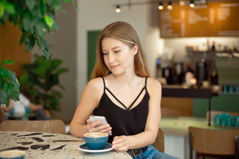 有长发的年轻美丽的金发碧眼的女人在魅力上面和牛仔裤喝咖啡并且看窗口 库存图片