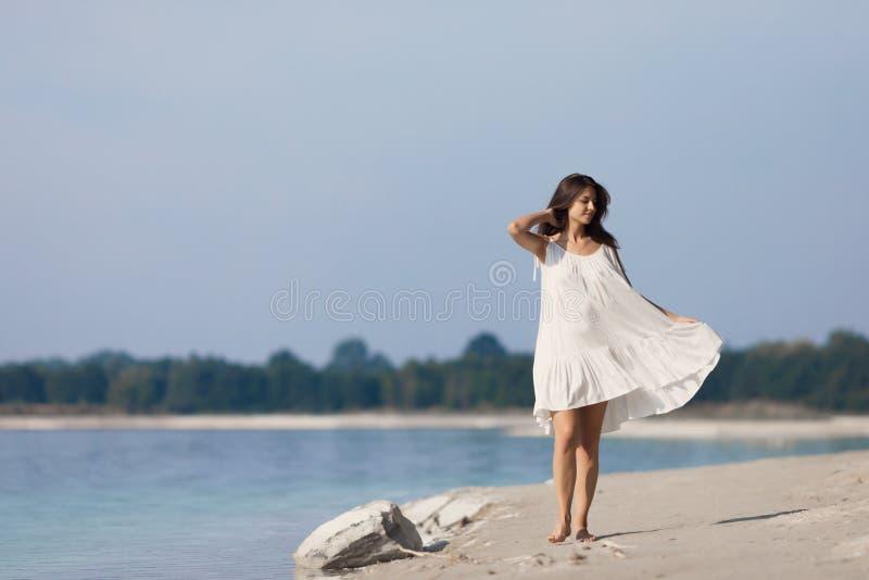 有长发的年轻美女在湖的一件白色礼服 免版税库存照片