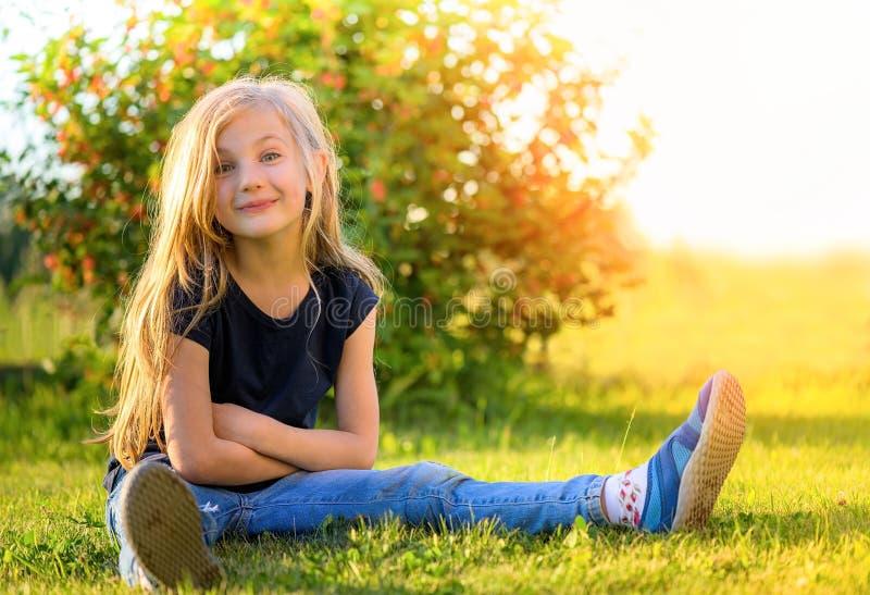 有长发的微笑的小白肤金发的女孩坐草 免版税库存照片