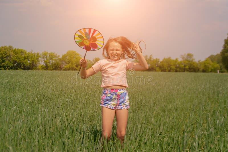 有长发的愉快的女孩在她手和跳跃上的拿着一个色的风车玩具 免版税库存照片