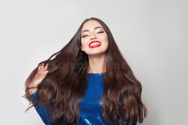 有长发的愉快的深色的妇女在白色背景 与健康发光的头发的美好的模型 库存图片