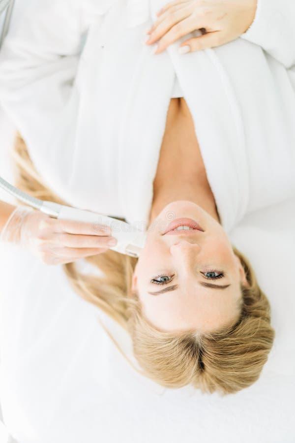 有长发的白肤金发的妇女做复出在美容中心的面孔激光 免版税库存照片