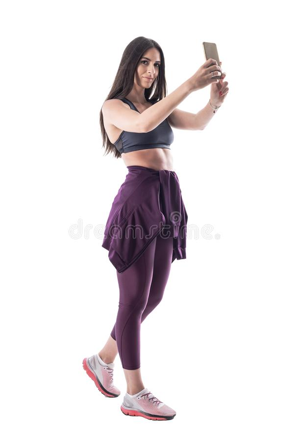 有长发的确信的性感的运动的适合的妇女在采取selfie的瑜伽裤子 免版税库存图片