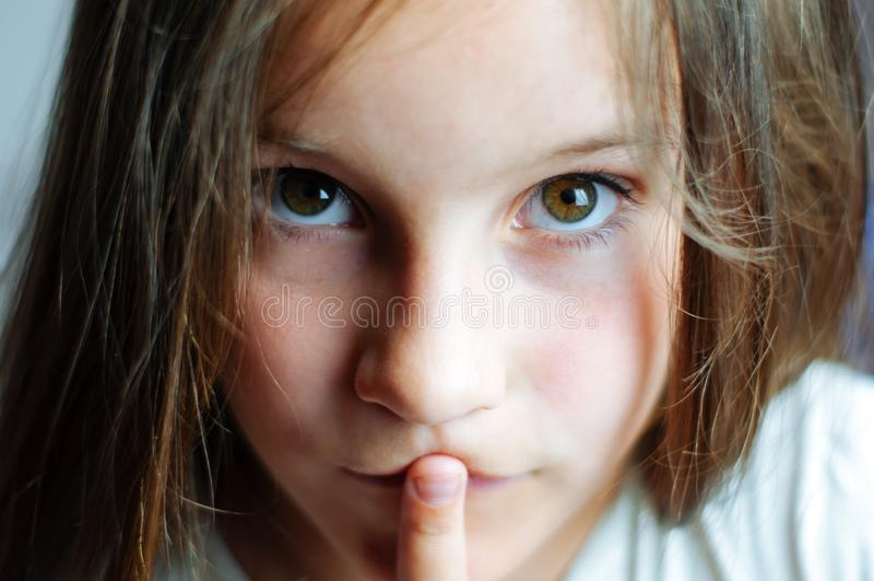 有长发的美丽的少女在她的嘴,接近的画象投入手指 免版税库存图片