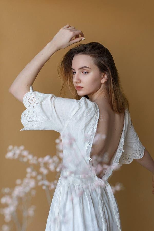 有长发的美丽的少女在摆在米黄背景的白色礼服 在前景的白花在焦点外面 库存照片