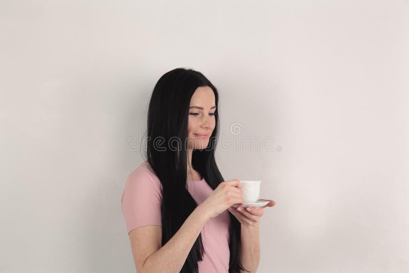 有长发的美丽的浅黑肤色的男人在外形在她的手上拿着一杯咖啡,她站立反对灰色背景 免版税库存图片