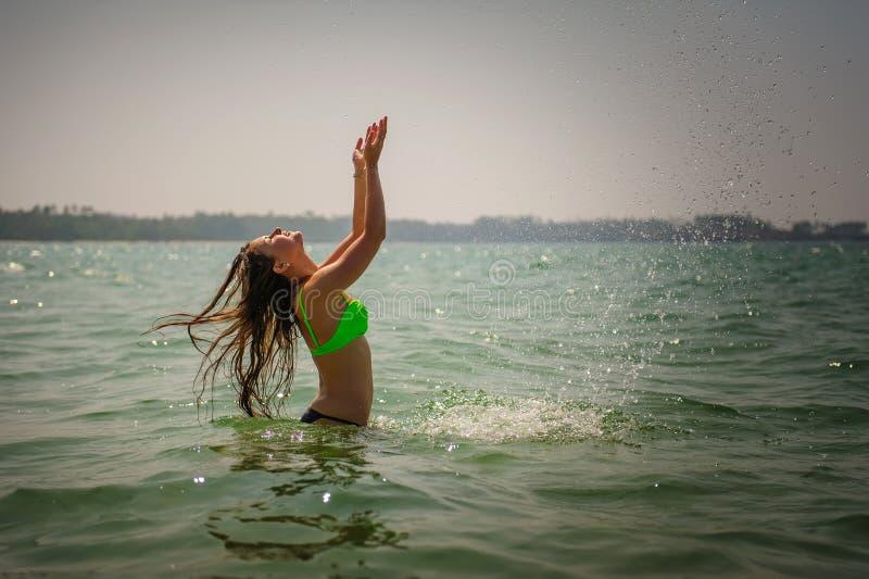 有长发的美丽的浅黑肤色的男人在水中站立腰部深在海洋并且飞溅她的手 明亮的年轻苗条女孩 免版税库存照片