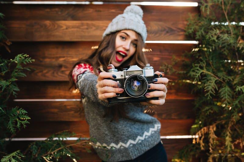 有长发的美丽的深色的女孩在获得的冬季衣服与照相机的乐趣在室外木的背景 ?? 免版税库存照片