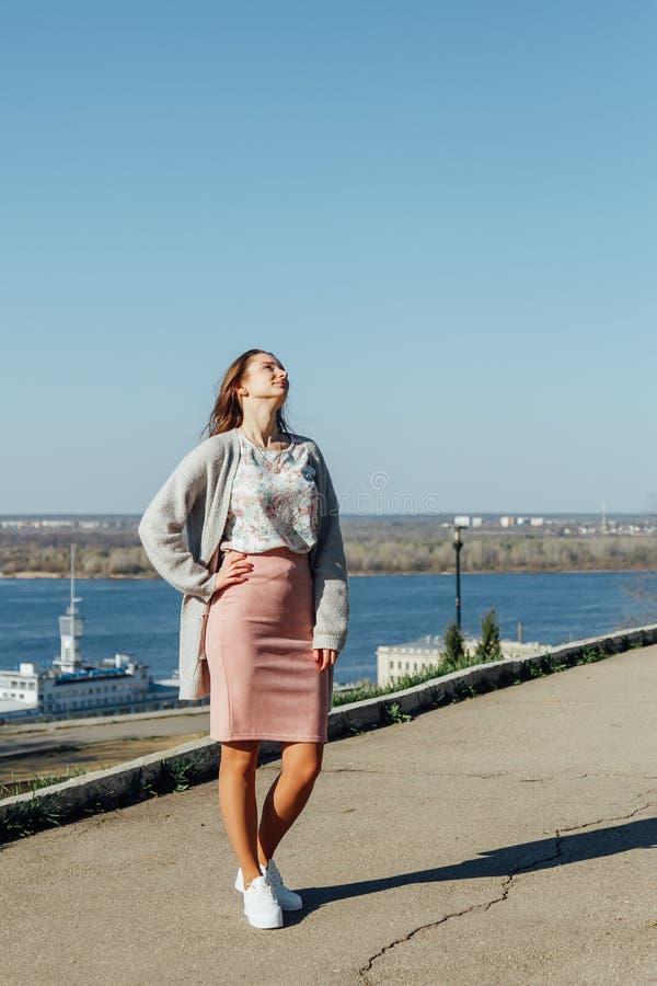 有长发的美女享受从桥梁的城市视图在一好日子 免版税库存照片