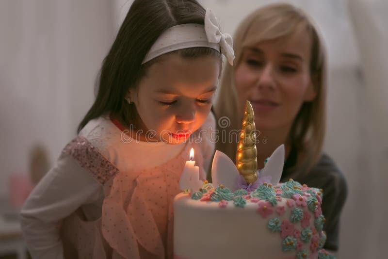 有长发的逗人喜爱的女孩有他的4岁生日 免版税库存图片