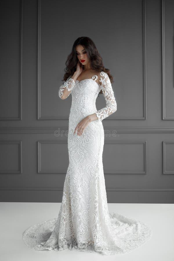 有长发的Elegan妇女在白色婚纱,他接触他的脖子用他的手,在灰色背景 免版税库存照片