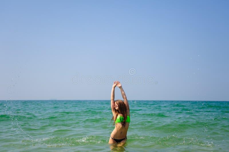 有长发立场的美丽的浅黑肤色的男人在举她的手的海和面对到太阳和天空 年轻被晒黑的女孩 免版税库存照片