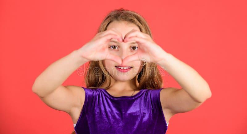 有长发笑容展示心脏姿态的孩子可爱的女孩对您 庆祝情人节 爱和同情 库存图片