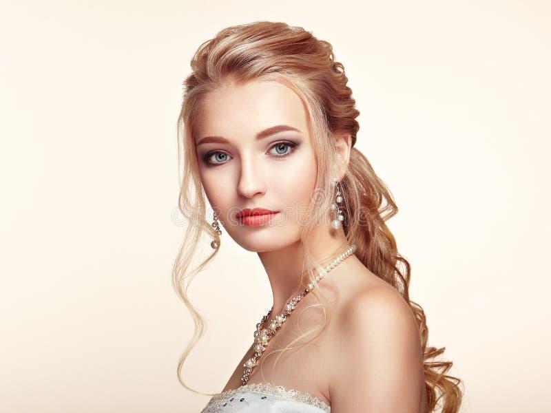 有长和发光的卷发的白肤金发的女孩 免版税图库摄影