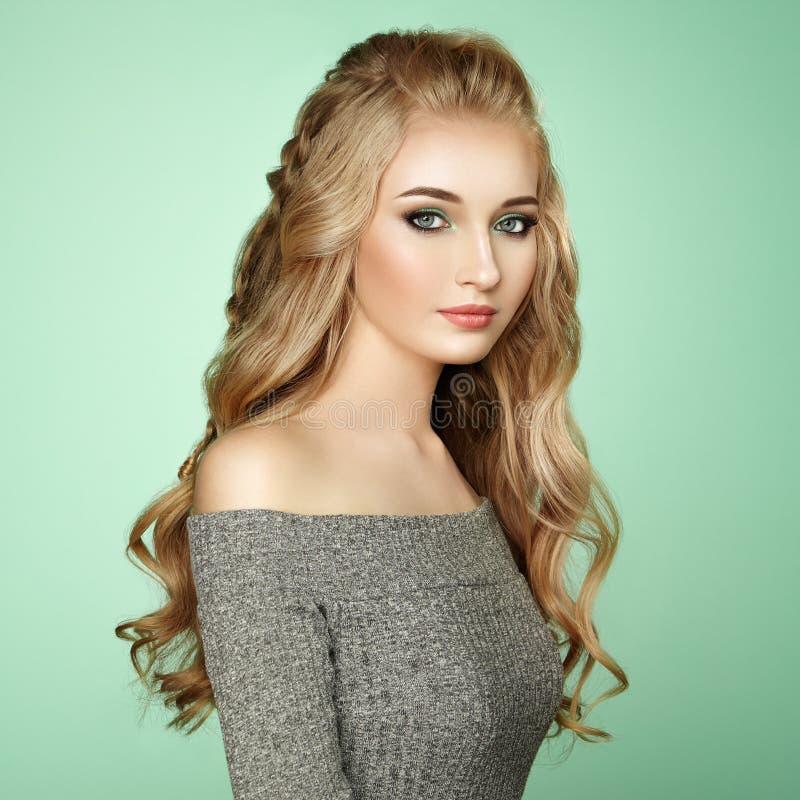 有长和发光的卷发的白肤金发的女孩 免版税库存图片