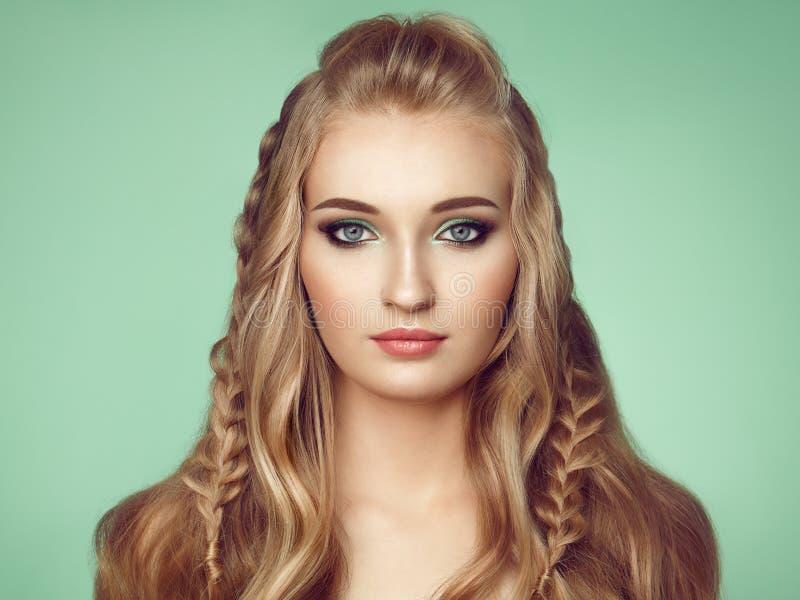 有长和发光的卷发的白肤金发的女孩 免版税库存照片