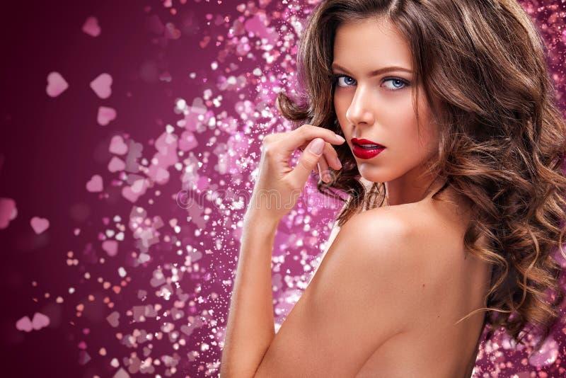 有长和发光的波浪发的性感的女孩 美好的模型,在红色背景的卷曲发型 St华伦泰` s日 免版税库存图片