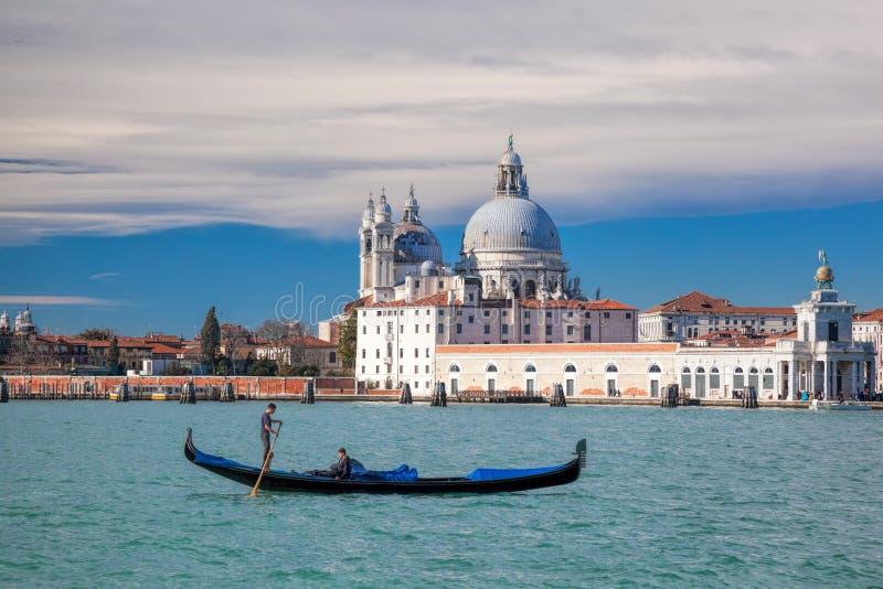 有长平底船的大运河反对大教堂圣玛丽亚della致敬在威尼斯,意大利 免版税库存图片