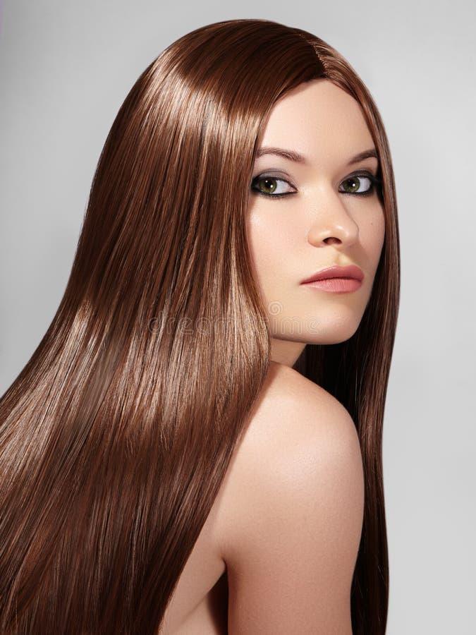 有长期平直的棕色头发的美丽的yong妇女 与光滑的光泽发型的性感的时装模特儿 与构成的秀丽 库存照片